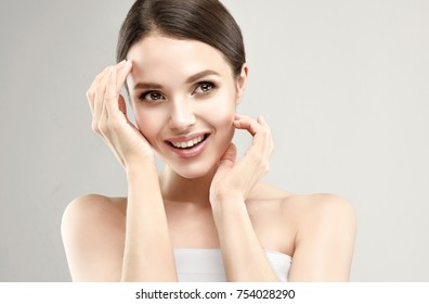 Gorgeous, young, brown haired woman with clean fresh skin and attractive, soft smile is touching  own face. Facial treatment, cosmetology, beauty technologies and spa.