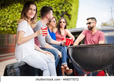 Gorgeous young brunette drinking beer with her friends at a barbecue and tailgating at a sports game