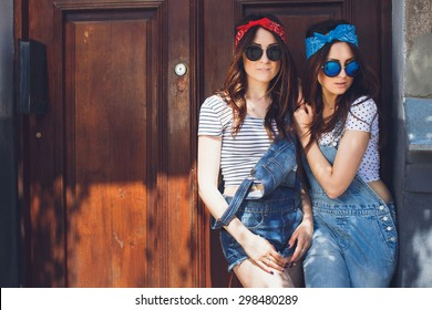 Gorgeous young brunette twins girls, in stylish sunglasses. Standing together. Wearing denim overalls bright bandanas, posing in front of old doors. Outdoors. Summer day. Copy space.