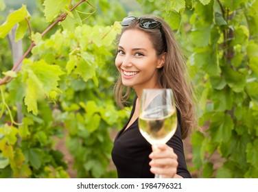 Herrliche junge Brunette Frau, die Wein genießt.