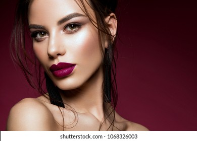 Gorgeous Young Brunette Woman face portrait. Beauty Model Girl with bright eyebrows, perfect make-up, purple lips. Sexy lady makeup for party.