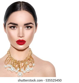 Gorgeous Young Brunette Woman face portrait. Beauty Model Girl with perfect bright make-up, red lips, golden jewellery with pearls. Sexy lady makeup for party. Isolated on white background.