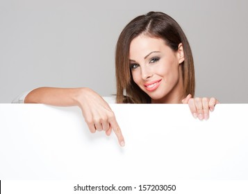 Gorgeous young brunette woman holding large blank white board with copy space.
