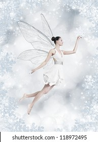 Gorgeous young brunette woman as winter fairy with wings on shiny silver background