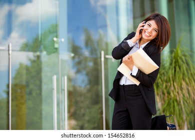 Gorgeous young business woman excited about a phone call and smiling