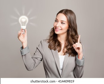 Gorgeous young businesswoman holding glowing light bulb idea symbol.