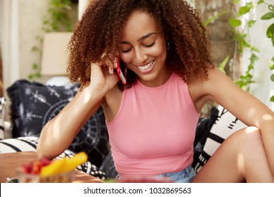 Gorgeous young dark skinned woman satisfied with good news while talks on mobile phone, rejoices having unforgettable vacations, feels relaxed on sofa, enjoys trip abroad. Communication concept