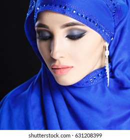 Gorgeous Young East Woman face portrait in hijab. Beauty Model Girl with bright eyebrows, perfect make-up. Traditional. Isolated on black background. Smokey.Jewelry on her face