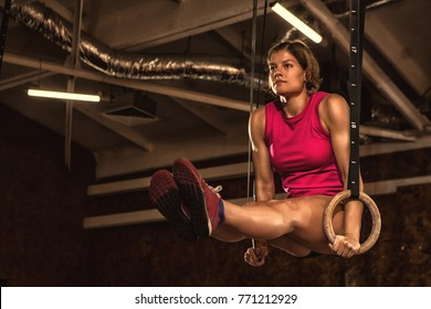 Gorgeous young female athlete with strong fit and toned body working out on gymnastics rings at crossfit gym looking concentrated and determined copyspace motivation athletics sports lifestyle fitness