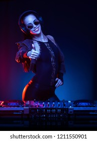 Gorgeous young female DJ in colorful stage lighting.