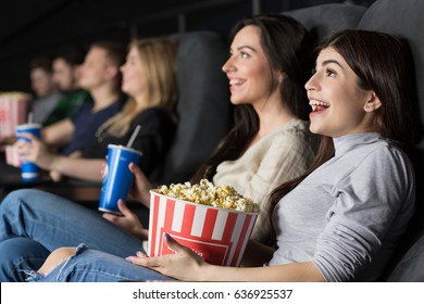 Gorgeous young female friends laughing happily enjoying a comedy movie together at the local cinema spending their weekend together copyspace friendship people youth fun entertainment movies industry