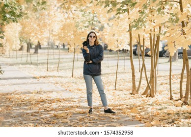 Gorgeous young female photographer in a blue raincoat, jeans, , and sunglasses holds the camera in bent hand and waits for the model in the sunny forest in the afternoon
