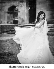 Gorgeous young female posing in a wedding dress. Happy wedding day. Exciting emotions in action.