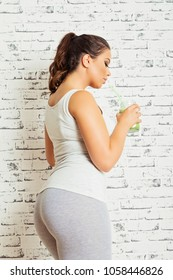 Gorgeous young fitness woman with green smoothie. Closeup, studio lighting, brick wall background.