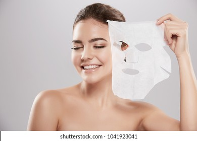 Gorgeous young girl  with naked shoulders posing at grey background with facial mask, skin care concept, beauty photo, skin treatment, hydrating skin mask, smiling.
