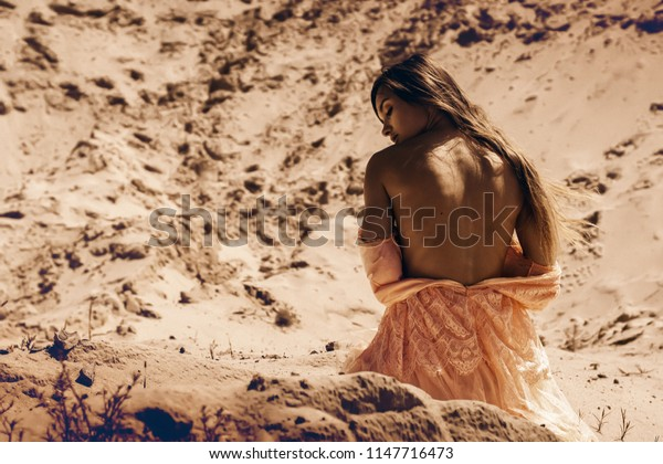 gorgeous young girl with nude back sits on a sand in desert