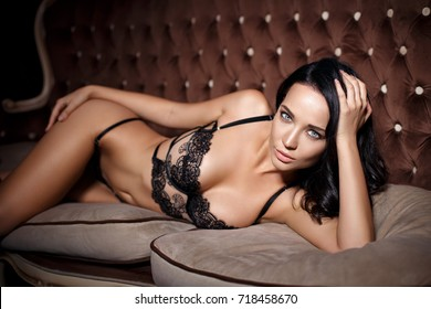 Gorgeous young girl in a sexy black lingerie on sofa
