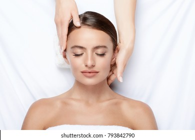 Gorgeous young girl with thick eyebrows and perfect skin doing facial massage, beauty photo concept, hands on face, skin care, stress free, treatment.