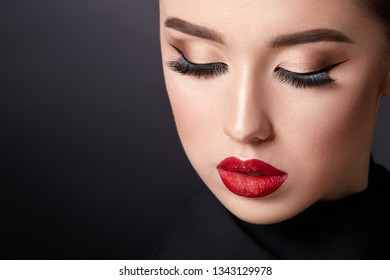 Gorgeous young girl wearing evening make up with red lips and long lashes at black studio background, close up.