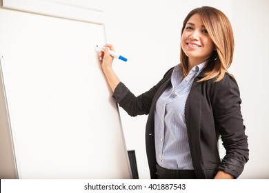 Gorgeous young Hispanic businesswoman writing on a flipchart and smiling during a business presentation