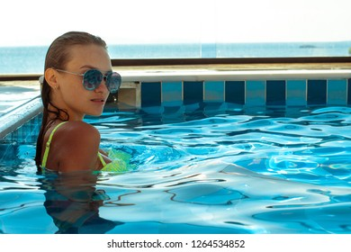 Gorgeous young lady at the pool posing