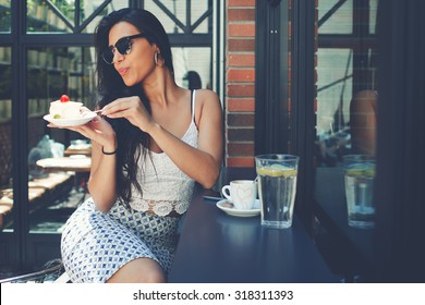 Gorgeous young latin woman dressed in stylish clothes and sunglasses sitting in a sidewalk cafe in summer while enjoying gentle sweet dessert and fresh water with lemon, female tourist eat sweet cake