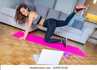 Gorgeous young latin woman sitting on exercise mat at home and watching workout tutorial online on laptop. Video lesson. Young woman repeating exercises while watching online workout session