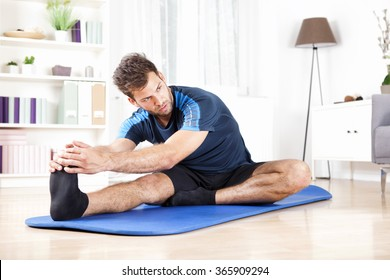Gorgeous Young Man Performing Hamstring Stretch Exercise at Home While Looking to the Right Side.