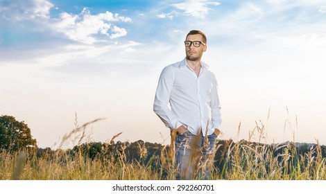 Gorgeous young man standing in a grass wearing white shirt, outdoors. Guy in nature, copyspace for text