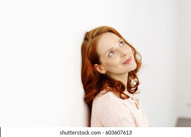 Gorgeous young redhead woman daydreaming as she stands leaning against a wall looking up with a smile