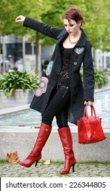Gorgeous Young White Woman Wearing Decorated Black Trench Coat with Red Leather Boots and Shoulder Bag. Strike an Outdoor Pose.