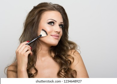 Gorgeous young woman applying makeup on her cheek using brush, smiling. No retouch, studio lighting.