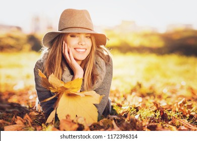 Gorgeous young woman in autumn in park with big yellow leaves, smiling and enjoying nature. Natural lighting, retouched, back light, closeup, copy space.