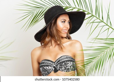 Gorgeous young woman in bikini and wide brim hat in tropical environment, palm leaves. Closeup portrait of beautiful Caucasian female model. Retouched, studio lighting.