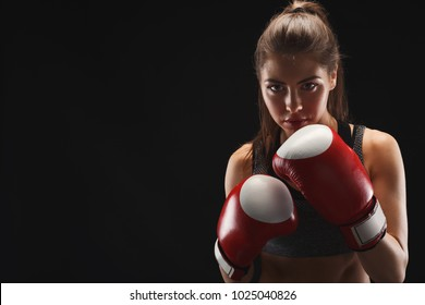 Gorgeous young woman with boxing gloves, standing in the defending position, ready to fight, copy space. Studio shot on black background, low key. Kickboxing and fight sport concept