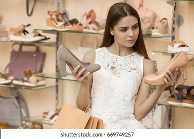 Gorgeous young woman choosing between two different shoes while shopping at the mall spree sale offer discount shopaholic bags consumerism customer buyer shopper wealth luxury style feminine