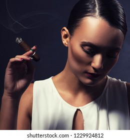 Gorgeous young woman with cigar. Dark studio background. Toned image