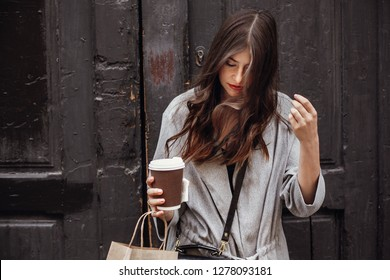 Gorgeous young woman with cup of coffee and bag standing at old wooden door in city street. Stylish happy hipster girl with beautiful windy hair enjoying time and shopping