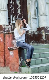 Gorgeous young woman with cup of coffee in city street. Coffee break. Coffee to go.