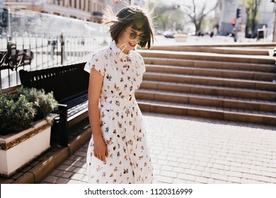 Gorgeous young woman in cute retro dress enjoying sunny morning. Outdoor photo of chilling brunette girl spending summer day outdoor in weekend.