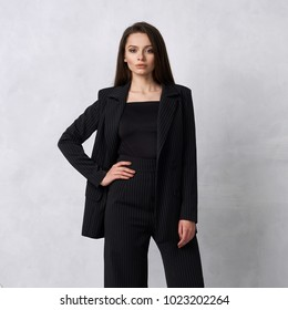 Gorgeous young woman dressed in black striped jumpsuit, blazer and heeled shoes posing in studio. Beautiful brunette girl demonstrating stylish smart clothing against white wall on background.