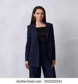 Gorgeous young woman dressed in blue squared jumpsuit, blazer and heeled shoes posing in studio. Beautiful brunette girl demonstrating stylish smart clothing against white wall on background.