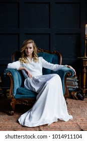 gorgeous young woman in elegant old-fashioned white dress posing while sitting in vintage armchair