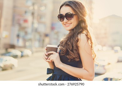 Gorgeous young woman enjoying some coffee while checking out the city
