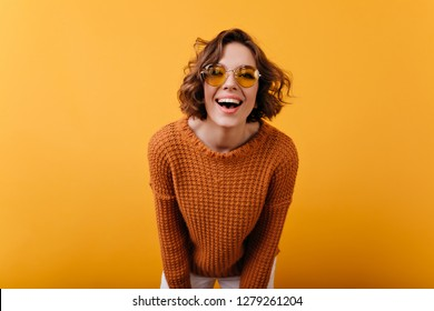 Gorgeous young woman in funny round glasses laughing to camera. Studio photo of joyful brown-haired girl with white skin wears knitted attire.