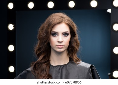 Gorgeous young woman with glamorous make-up in pelerine looking at camera