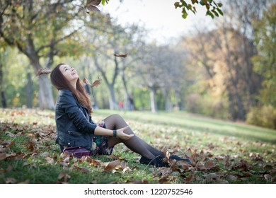 Gorgeous young woman having great time in autumn sunny day in the park.