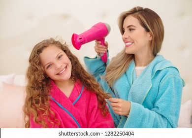 Gorgeous young woman with her daughter while she is holding a hair dryer. Adorable young girl posing with her mom at the room