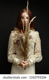 gorgeous young woman holding dry reed and posing