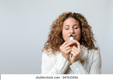 Gorgeous young woman holding a small bottle and smelling the aroma, over grey